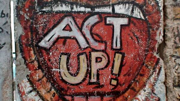 Ein Act Up-Graffiti an der Berliner Mauer. Foto: Rory Finneren from Washington, DC (Act Up!) [CC BY 2.0 (http://creativecommons.org/licenses/by/2.0)], via Wikimedia Commons